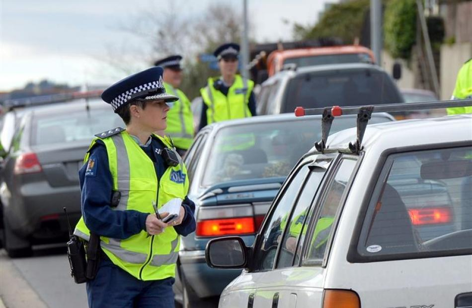 Inspector Mel Aitken, of Dunedin, checks registration details during a checkpoint on Kaikorai...