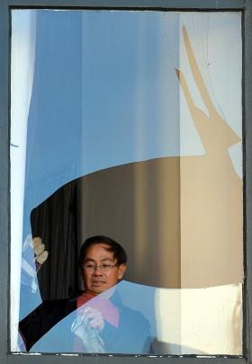 Investment House owner Tony Tan inspects a broken window. Photo by Peter McIntosh