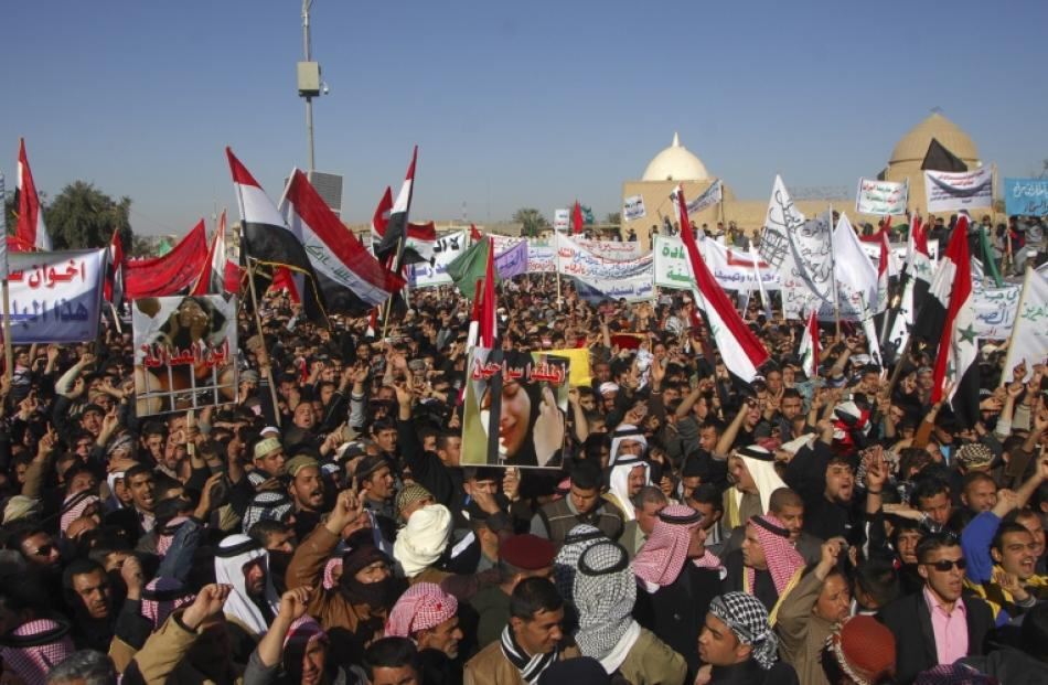 Iraqi Sunni Muslims wave national flags and chant slogans during an anti-government demonstration...
