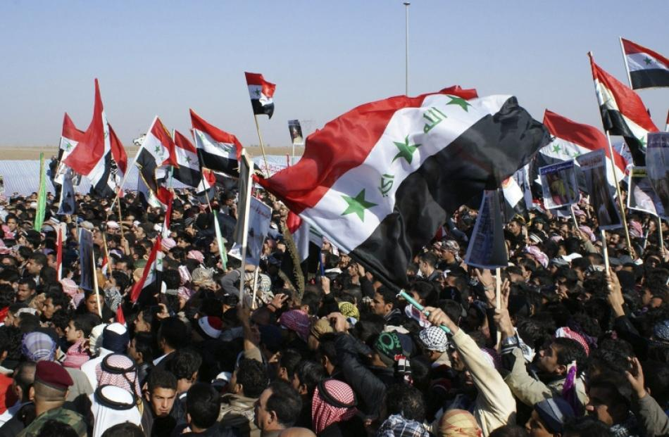 Iraqi Sunni Muslims wave the old flag of Iraq during an anti-government demonstration in Ramadi,...