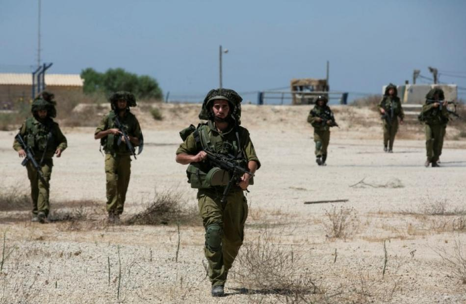 Israeli soldiers walk near the border with the central Gaza Strip. REUTERS/Baz Ratner
