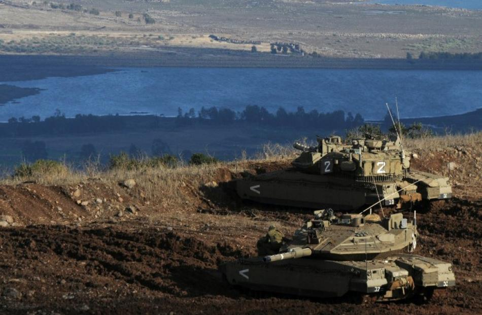Israeli tanks stand in position overlooking a Syrian village from the Israeli-occupied Golan...