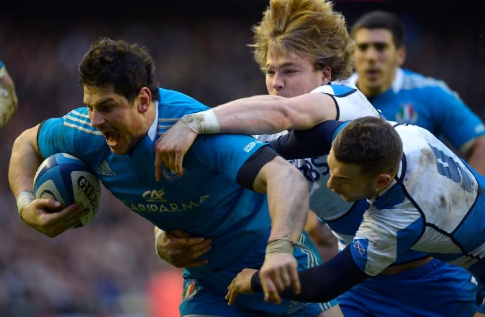 Italy's Alessandro Zanni scores a try despite the attentions of Scotland's David Denton and Greig...