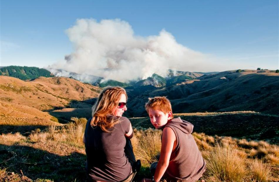 Jeannine Falloon and Daniel Dickson watch the fire from their neighbouring property yesterday....