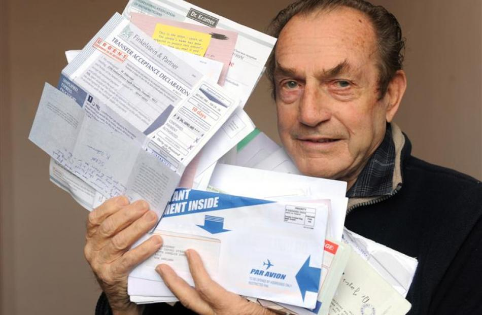 John Alderman (85) holds some of the scam mail he gets daily in his South Dunedin letterbox....