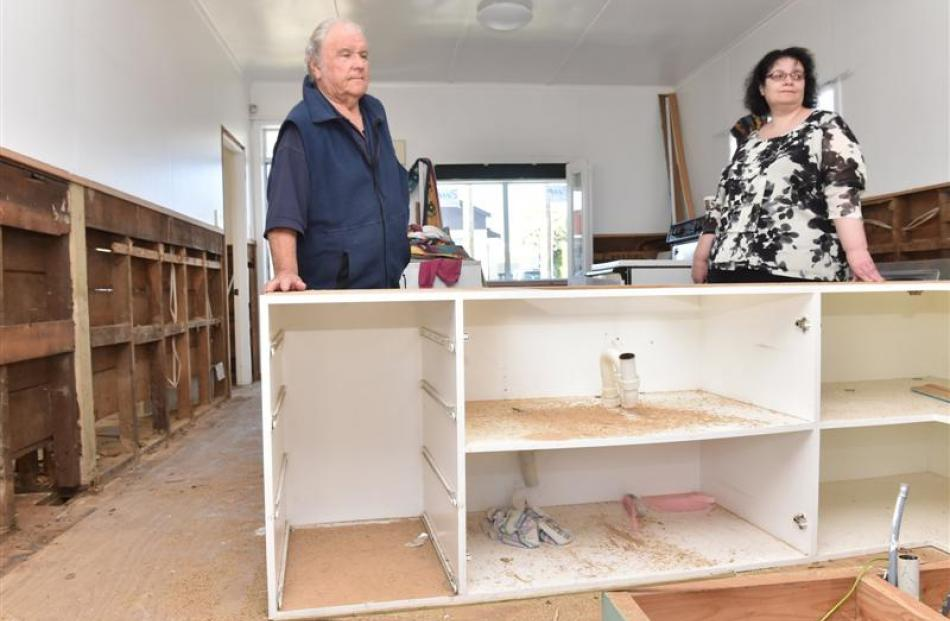 John Duff and his daughter, Jo, stand in the Nelson St house badly damaged by the June 3 flood....