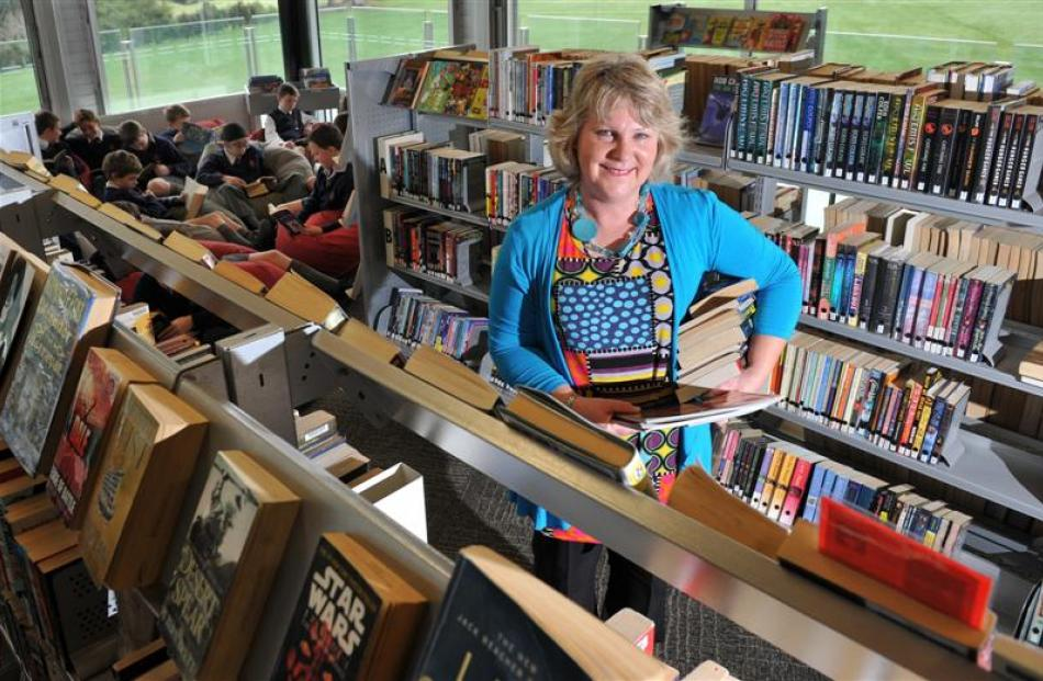 John McGlashan College library manager Pam Garry continues to stack books after winning the...