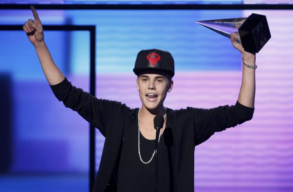 Justin Bieber accepts the award for favorite pop rock album for 'Believe' at the 40th American...