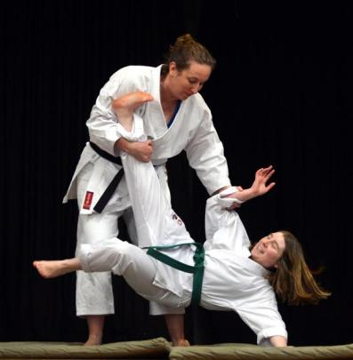 Karate black belt and physicist Emily Hall (standing) gives Queen's High School pupil Suzanne...