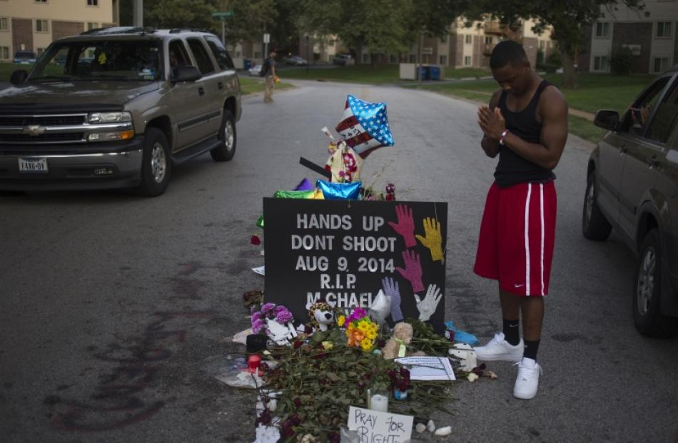 Ken Kendricks Jr., a nearby resident, puts his hands together in prayer at a makeshift memorial...