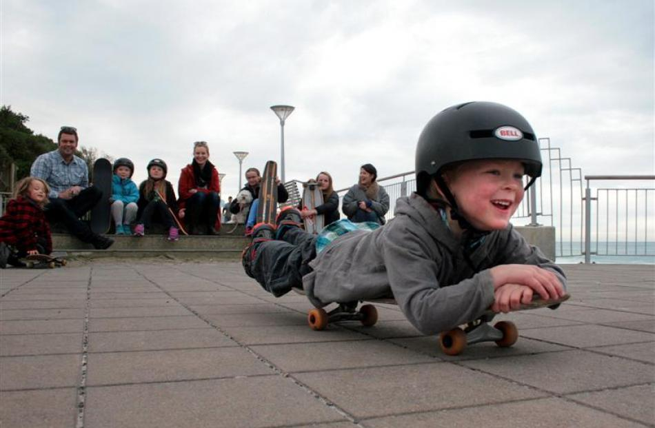 Keo Morrison (4) rolls along the St Clair Esplanade on his skateboard with other local surfers...
