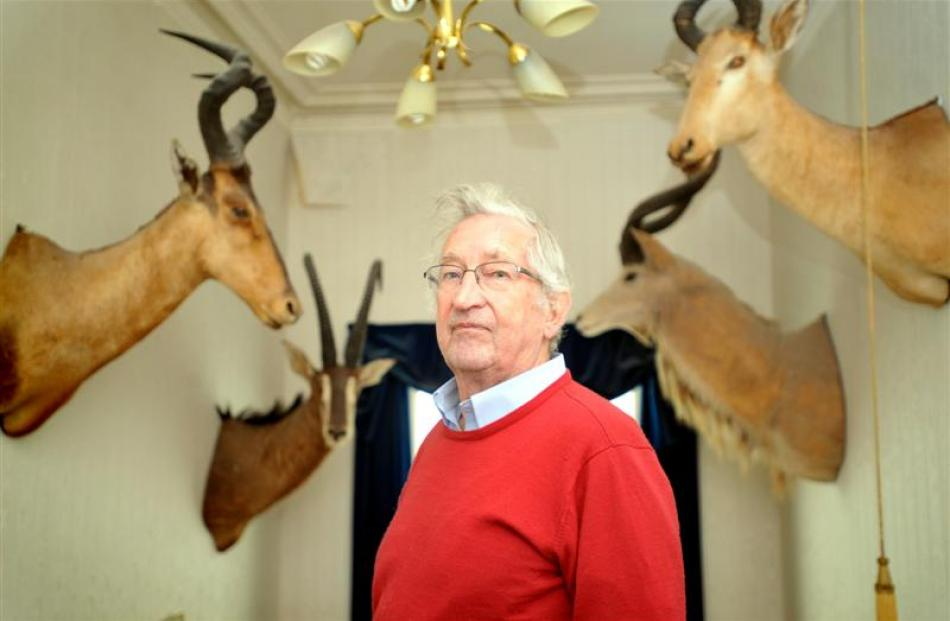 Kevin Shannon stands below some of the  game trophies he has collected over the years. Photo by...