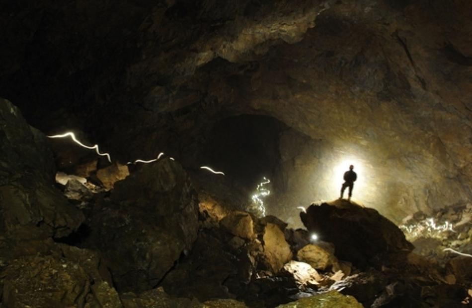 Kieran Mckay is dwarfed in a huge Stormy Pot-Nettlebed cave. Photo: Jonathon Ravens/NZ Herald
