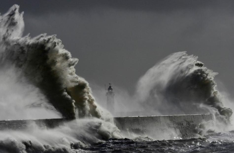 Large waves hit the lighthouse and harbour at high tide at Newhaven in Sussex, southern England....