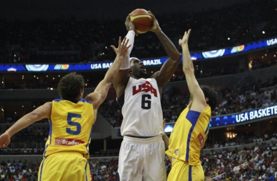 Lebron James of Team USA (centre) goes up against Raulzinho (left) and Guilherme Giovannoni of...