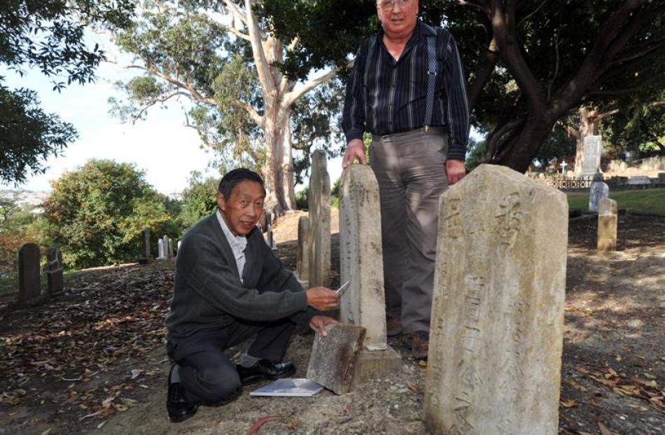 Leslie Wong (left) and Stewart Harvey inspect a restored headstone at the Southern Cemetery....