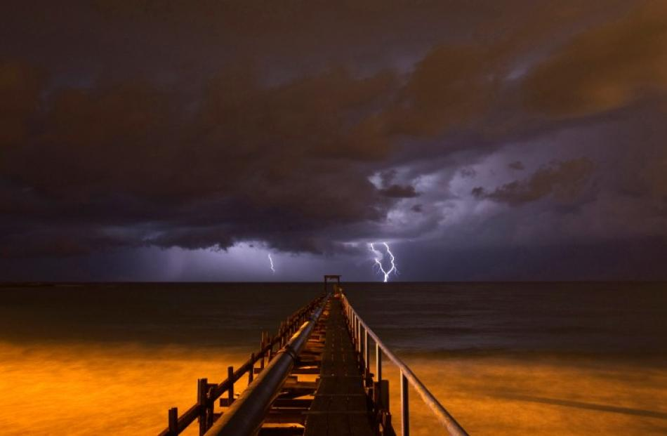 Lightning strikes over a pier during a storm in Atlit, near the northern Israeli city of Haifa in...