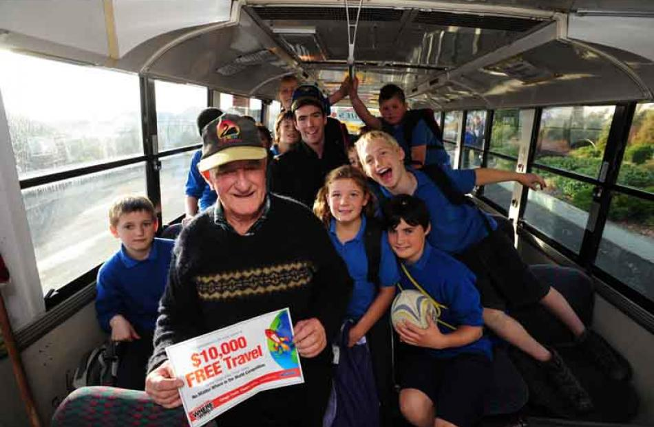 Lindsay Wright and Balclutha Primary School pupils on his bus celebrate his big travel win,...