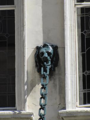 A lion's heads grasps an iron chain holding up a verandah.