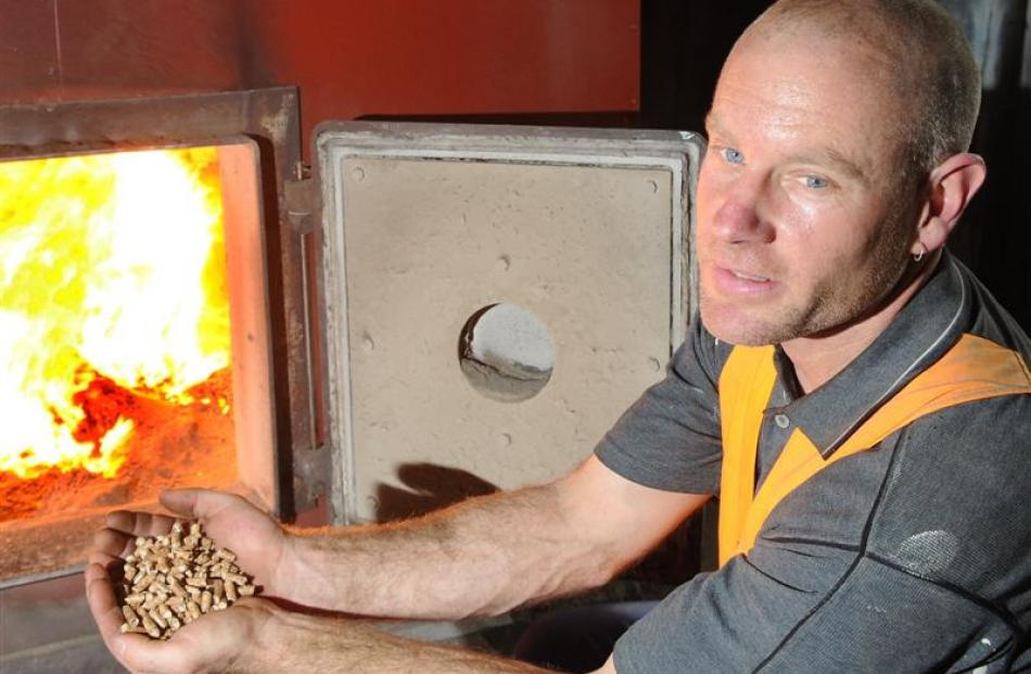 Logan Park High School property site manager Dave Penny with wood pellets for the school's boiler...