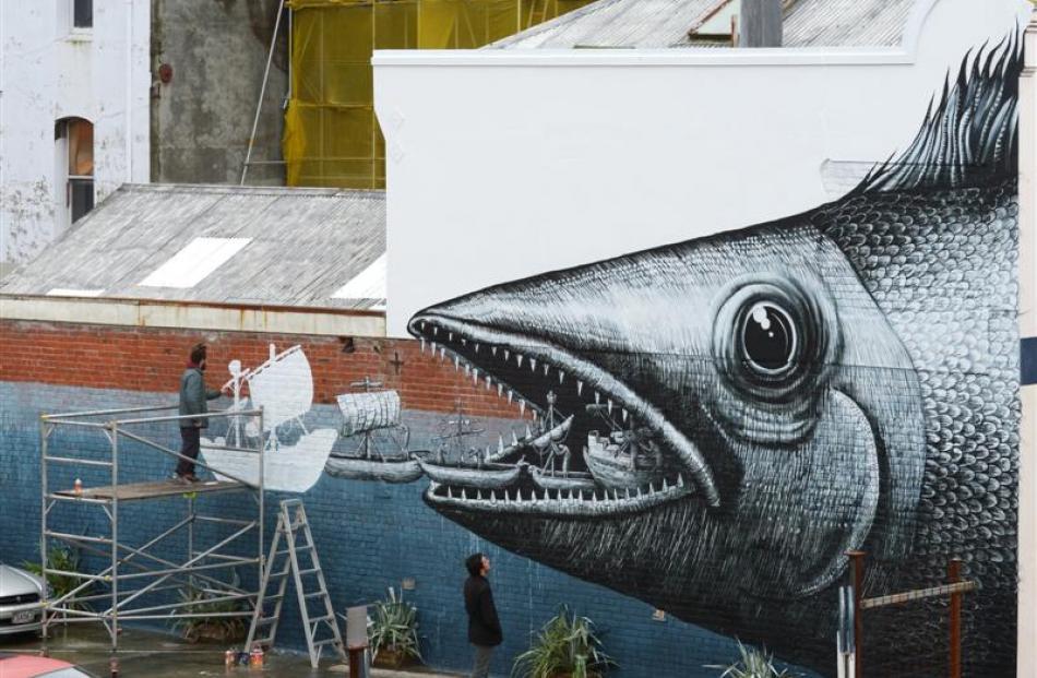 London  artist Phlegm (left) works on a mural on the former Rogan McIndoe building in Vogel St,...