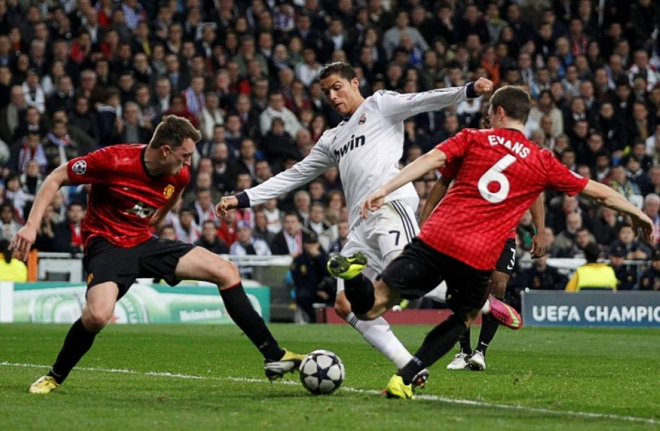 Manchester United's Phil Jones (L) and Jonny Evans stop Real Madrid's Cristiano Ronaldo from...