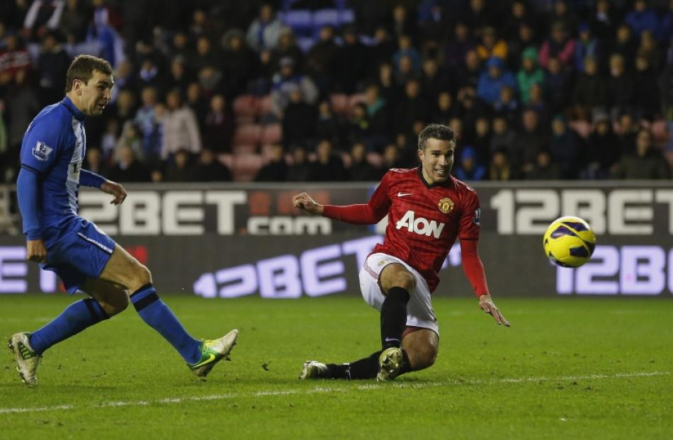 Manchester United's Robin Van Persie (right) shoots to score against Wigan Athletic during their...