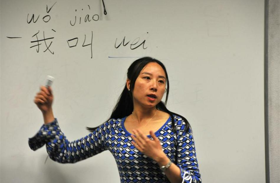 Mao Wei gives a lesson in Chinese writing. The  characters read: ''My given name is Wei''. Photos...