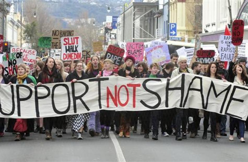 "Marchers walk down George St on Saturday during the Dunedin Rape Crisis ""Slutwalk"" rally against..."