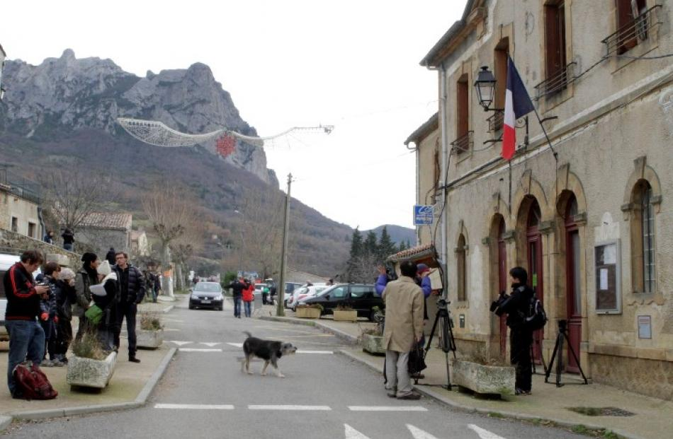Members of the media stand outside the town hall in Bugarach, France. Some people believe the...