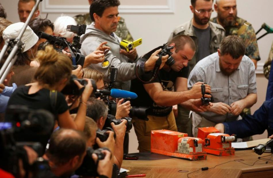 Members of the media take pictures of black boxes belonging to Malaysia Airlines flight MH17,...