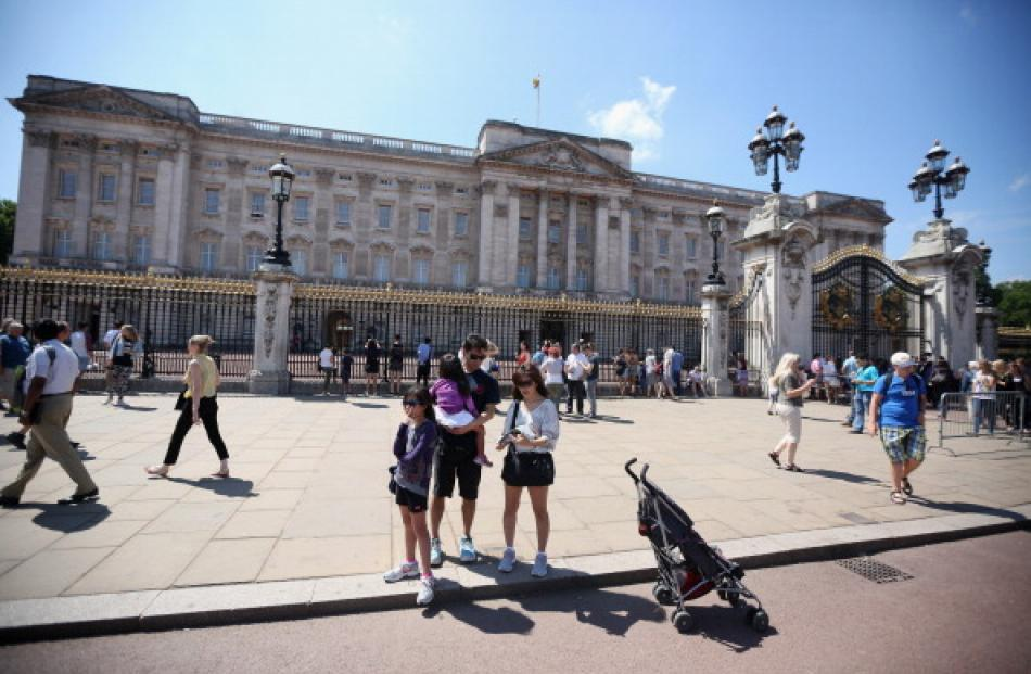 Members of the public admire Buckingham Palace. Photo Getty Images