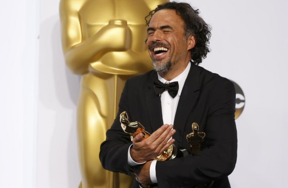 """Mexican Director Alejandro G. Inarritu holds his three Oscars for for his film """"Birdman"""" which..."""
