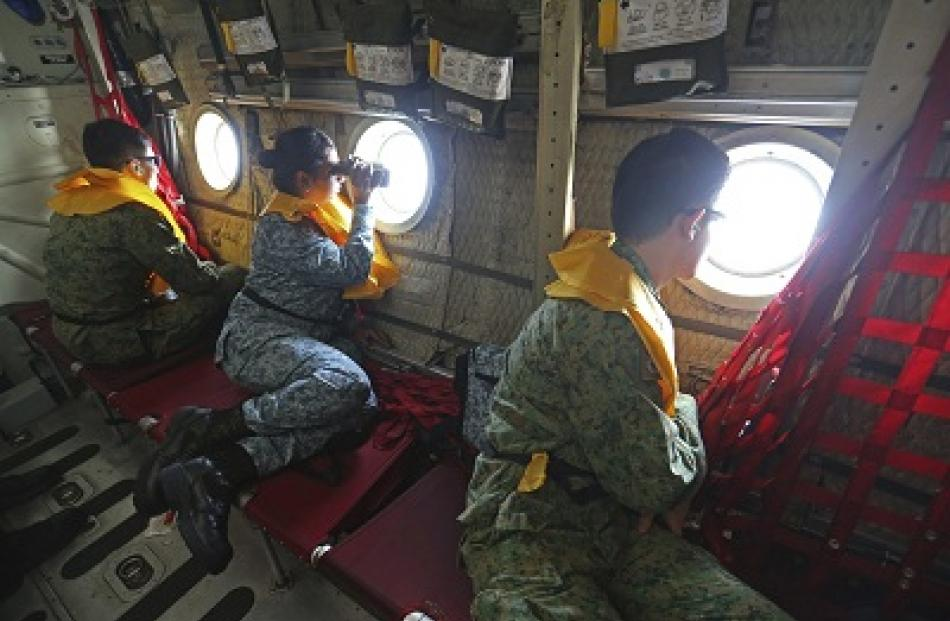 Military personnel search for the missing Malaysia Airlines MH370 plane over the South China Sea....