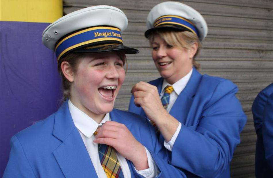 Mosgiel Brass member Cathy Bennett makes some last-minute adjustments to daughter Sam's uniform...
