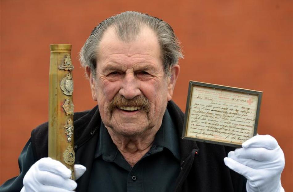 Mosgiel resident Bing Crosbie (83) holds an item of military memorabilia - New Zealand regimental...