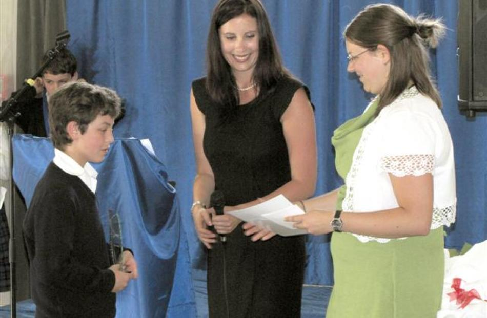 Munro D'Aiello (12) is awarded his trophy and certificate by principal Rebekah Key (centre) and...