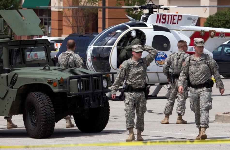 National Guard troops walk through a staging area inside a shopping centre parking lot in...