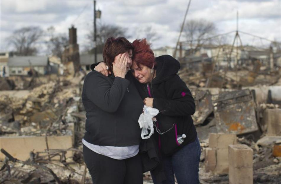 Neighbours Lucille Dwyer (right) and Linda Strong embrace after looking through the wreckage of...
