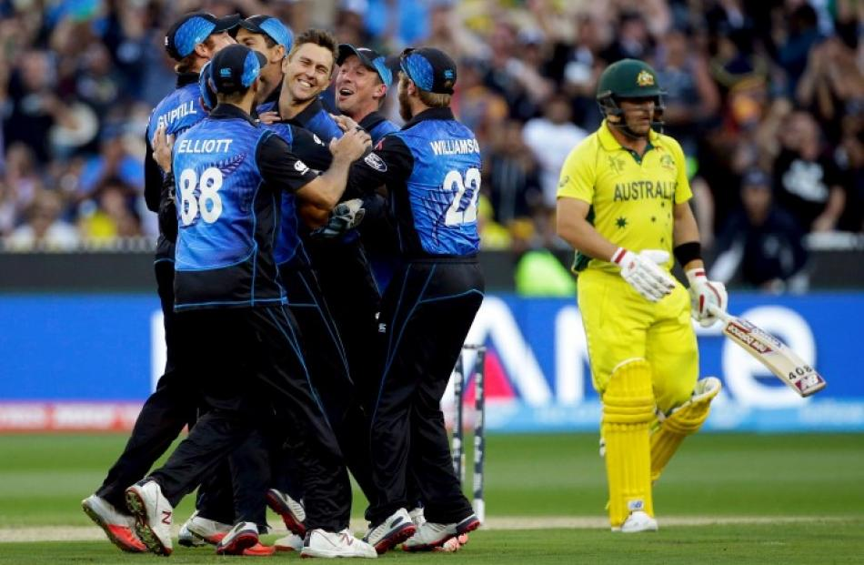 New Zealand's Trent Boult (C) is surrounded by teammates as they celebrate his dismissal of...