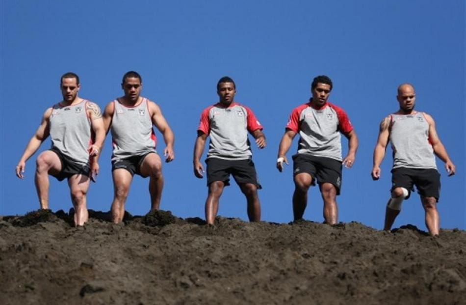 New Zealand Warriors players take a rest as they train on the sand dunes at Bethells Beach in...