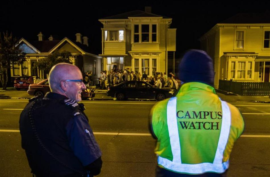 Noise control officer Rex Johnston stands with a campus watch officer in front of a student party...
