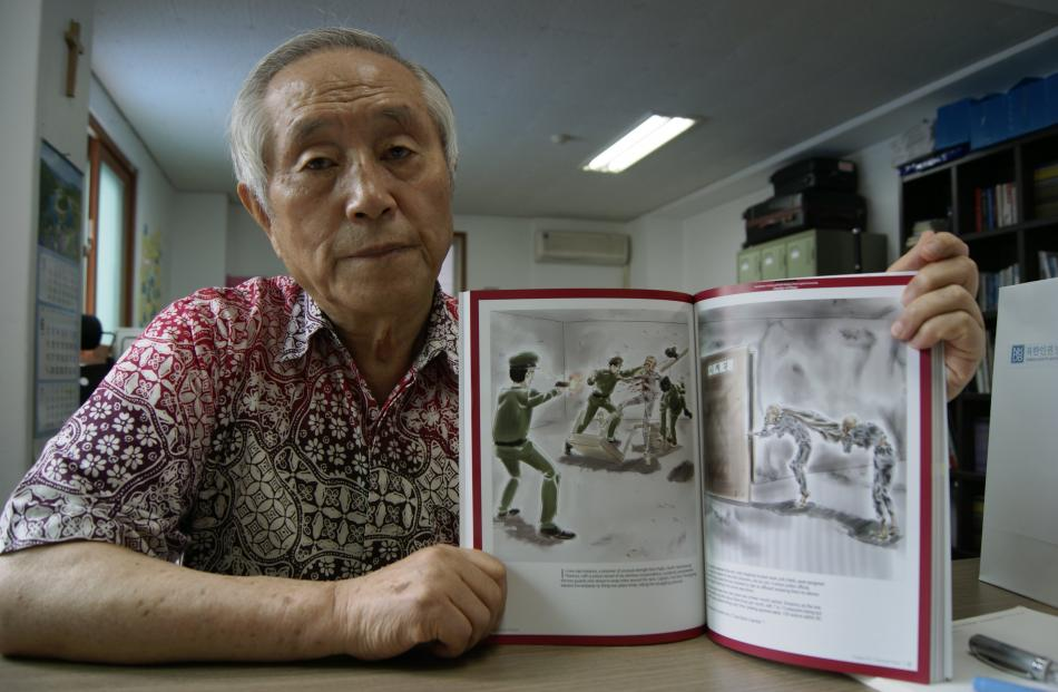 North Korean exile Kim Sang Hun with his book detailing abuse in the secretive country. Photo by...