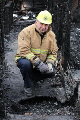 North Otago fire safety management officer Stu Ide inspects the  historic homestead destroyed by...
