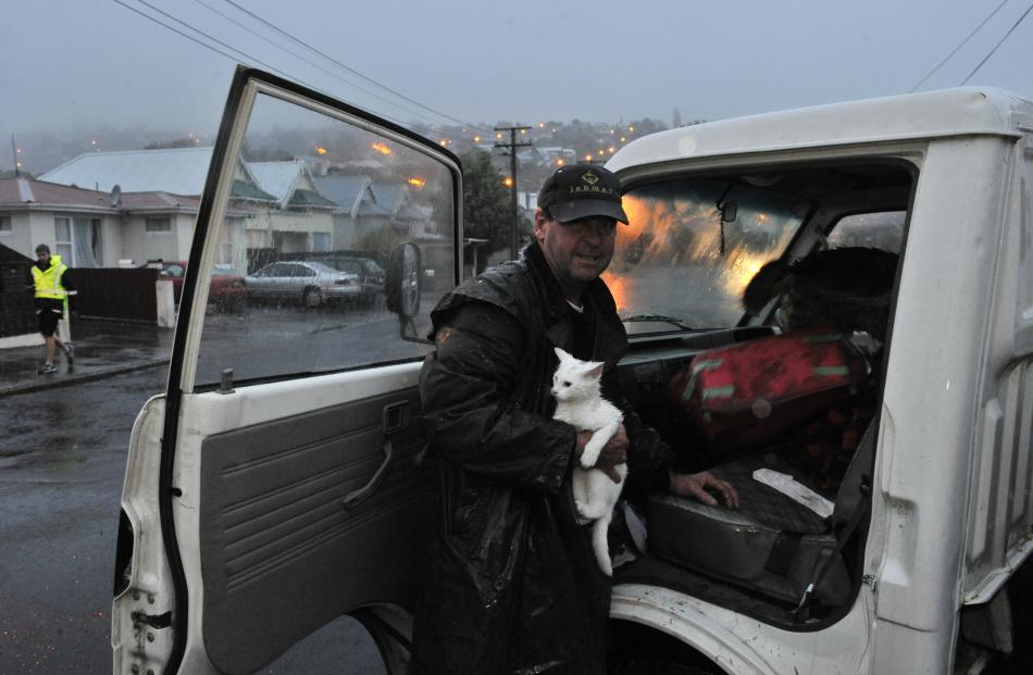 Northeast Valley resident Marty Duffy leaves  with his cat Honky after a slip opened up a '...