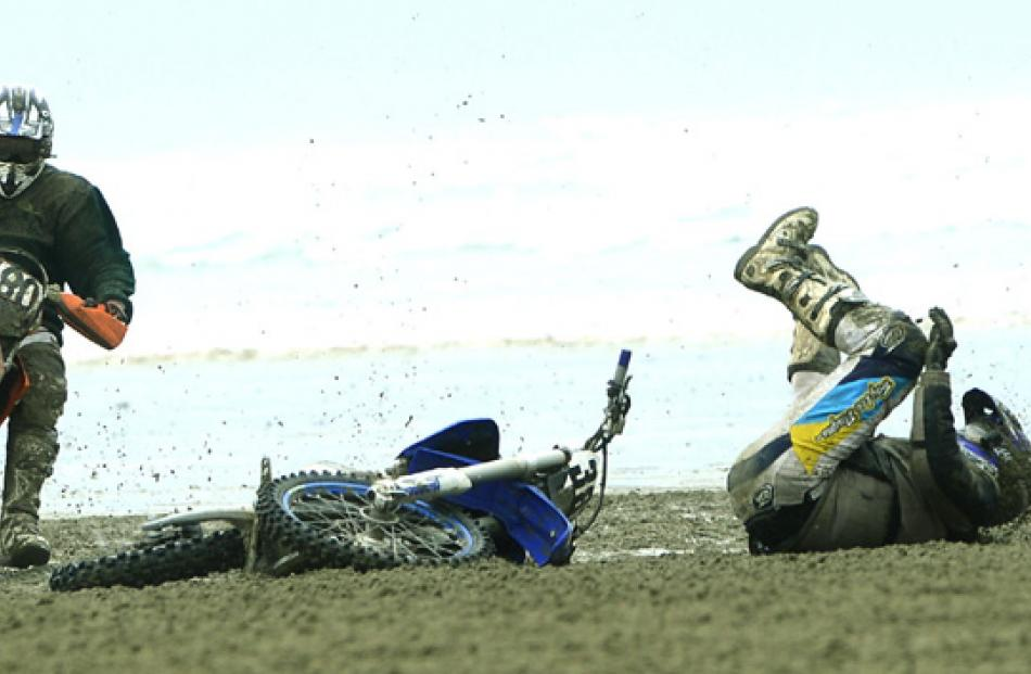 Number 380, Ryan McKenzie of Wyndham, on his Husaberg FE 570 falls off while watched by number...