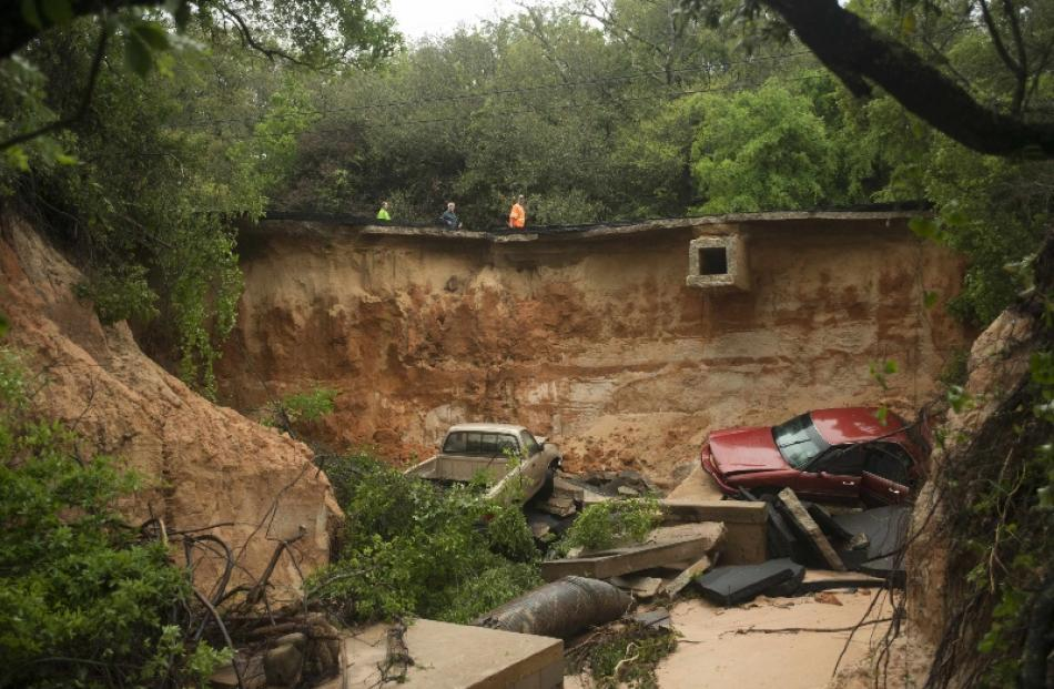 Officials look at the washed out area of Scenic Highway 90 after heavy rains and flooding damage...