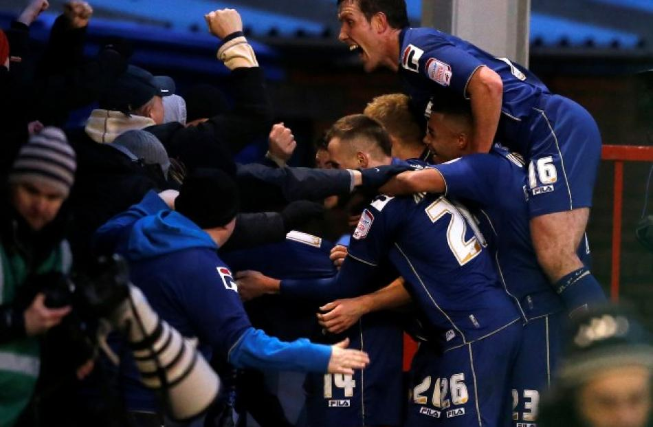 Oldham Athletic's Matt Smith (hidden) celebrates with teammates and supporters after scoring his...