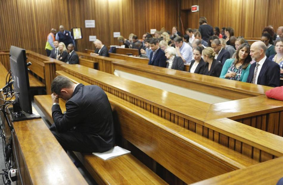 Oscar Pistorius clasped his head between his hands as lead defence lawyer Barry Roux read out...
