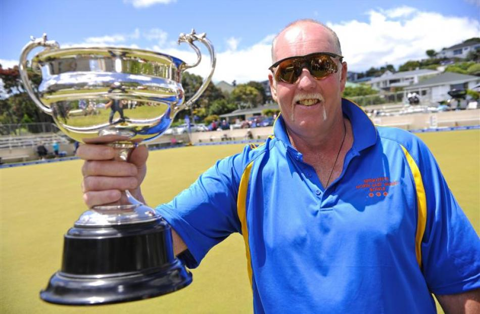 Otago bowler Shaun Scott celebrates with the trophy after winning the singles final at the New...